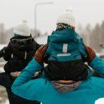 ulkoilua, äiti ja isä kävelevät lapset harteilla talvisessa maisemassa