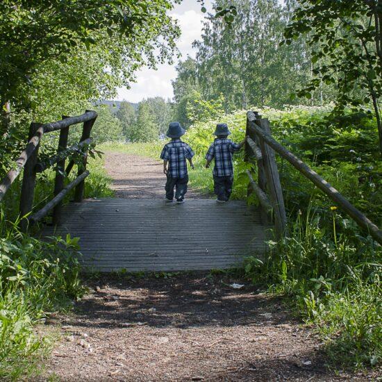 kaksospojat kävelevät sillalla