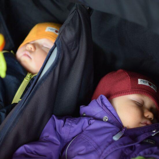 kaksi vauvaa nukkuu ulkovaatteissa lastenvaunuissa