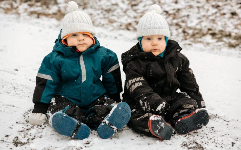 kaksoset, taaperot, istuvat talvihaalareissa lumessa
