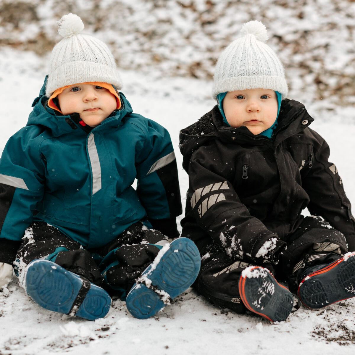 kaksoset istuvat maassa, pipot päässä