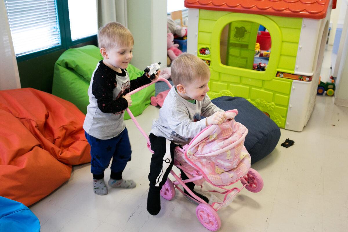 kaksoset, kaksospojat leikkivät nukenrattailla