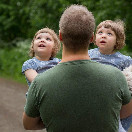 monikkoperhe, isä selin, kaksostytöt sylissä