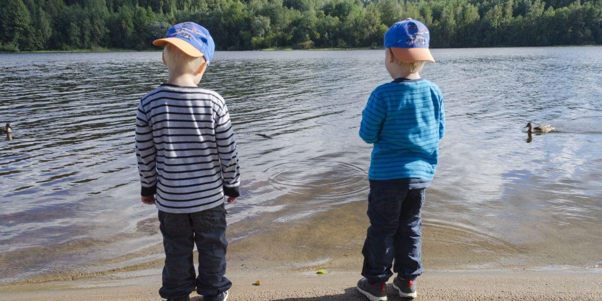 kaksi poikaa rannalla lippalakit päässä katselemassa sorsia