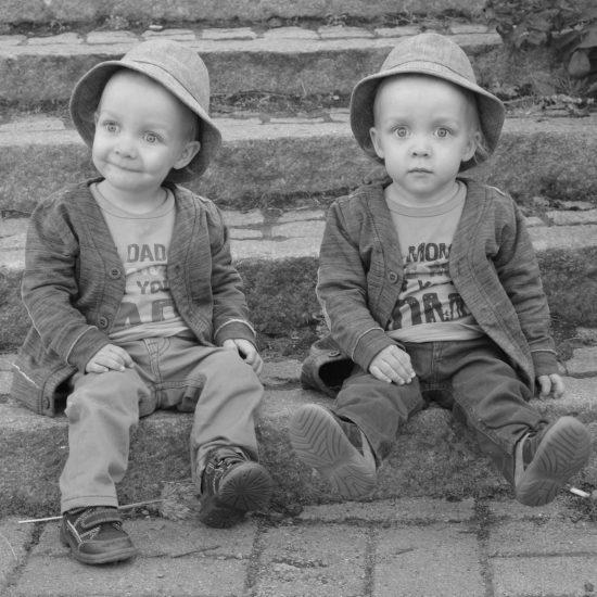 pienet kaksospojat istuvat portailla hatut päässä