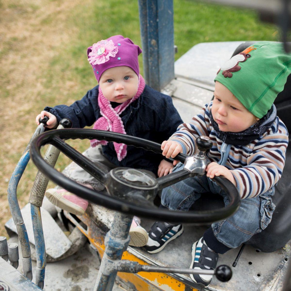 kaksoset, tyttö ja poika, traktorin ohjaimissa