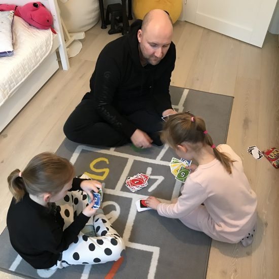 Isä ja lapset pelaavat korttia