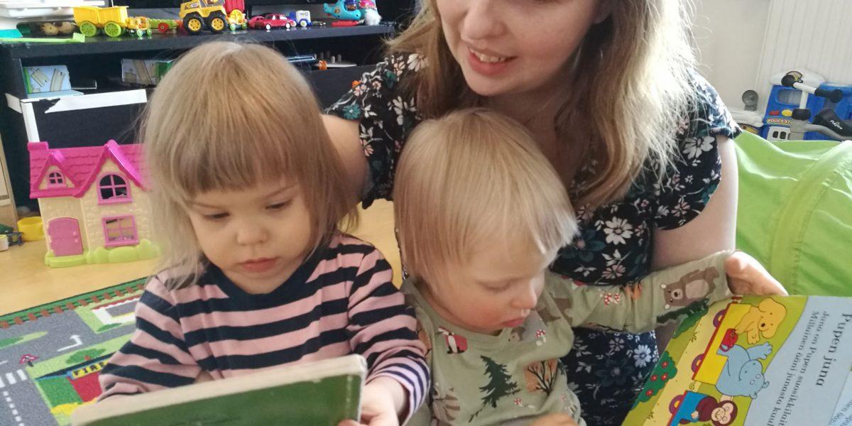 Äiti sylissään kaksi pientä lasta