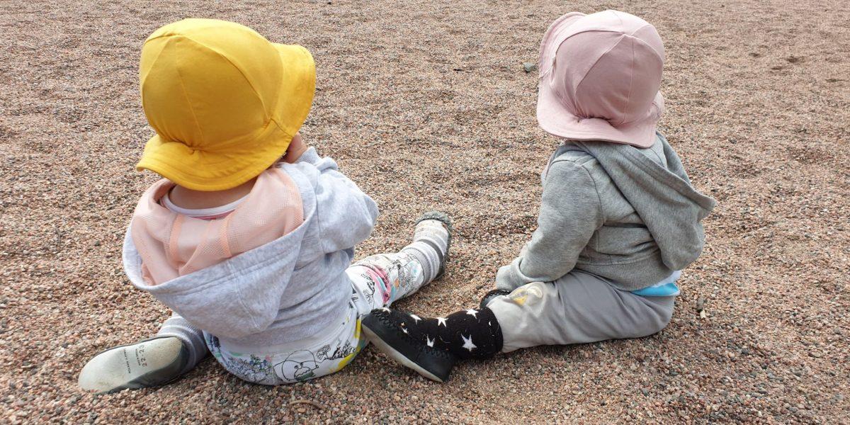 Taaperoikäiset kaksoset hiekalla selin lierihatut päässä.