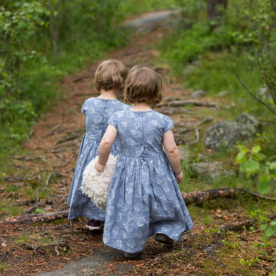 pienet kaksostytöt, selin, kävelevät samanlaiset siniharmaat mekot päällä pitkin kesäistä metsäpolkua.